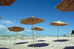 Straw umbrellas with shadow on the beach. On blue sky background in summer season Stock Photo