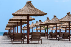 Straw umbrellas sun-beds on beach Royalty Free Stock Photo
