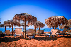 Straw umbrellas and sunbeds on a sandy beach in Greece Stock Photos