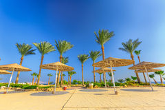 Straw umbrellas and sunbeds on the wonderful tropical beach. Royalty Free Stock Image