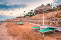 Straw umbrellas and sunbeds on the wonderful tropical beach. Royalty Free Stock Images