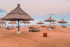 Straw umbrellas and sunbeds on the wonderful tropical beach. Stock Image