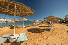 Straw umbrellas and sunbeds on the wonderful tropical beach. Royalty Free Stock Photos