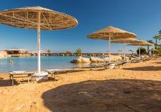Straw umbrellas and sunbeds on the wonderful tropical beach. Stock Photos