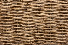 Straw weaved mat texture. Tan straw horizontal over under weaved mat with fiber texture with irregularities royalty free stock photos