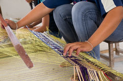 Straw weaving. Young women in Thailand weaving a matt from straw on a simple weave royalty free stock image