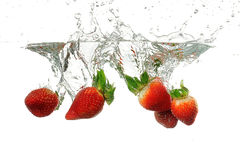 Strawbarries being dumped into water. Strawberries being dumped into water with splashes on a white background Royalty Free Stock Image