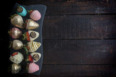 Strawbeeries in colorful chocolate. On wooden background with blank space stock photography
