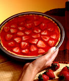 Strawberrie pie. A hand holding a strawberrie pie royalty free stock photography