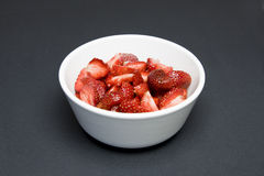 Strawberries. Some sliced strawberries in white bowl; isolated on black Royalty Free Stock Photo