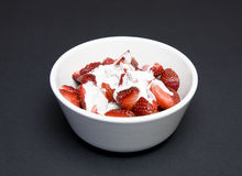 Strawberries. Some sliced strawberries with cream in white bowl; isolated on black Royalty Free Stock Photo