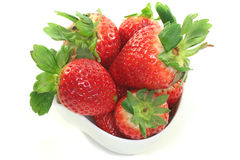 Strawberries. In a bowl on a white background stock images