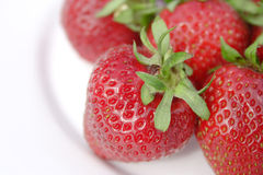 Strawberries. Four juicy strawberries on a white plate, view from above with focus on front two strawberries, landscape format Royalty Free Stock Image