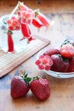 Strawberries. Two strawberries and red flowers Royalty Free Stock Image