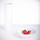 Strawberries. Studio shot of a bowl, a vase and two strawberries Stock Images
