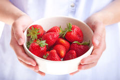 Strawberries. Young woman holding a bowl of fresh strawberries Stock Images