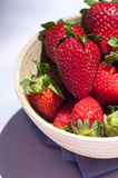 Strawberries 3. Strawberries in a wood bowl and purple towel Royalty Free Stock Photo