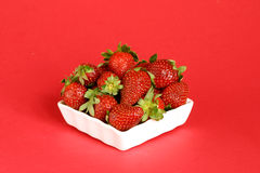 Strawberries. Fresh strawberries in a ramekin on a red background Stock Photos