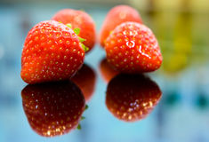 Strawberries. Some red strawberries lying on glass surface Royalty Free Stock Photography