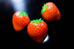 Strawberries. Some red strawberries lying on black surface Royalty Free Stock Image