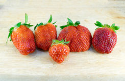Strawberries. Abnormal strawberries shape put on the wood background stock image