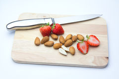 Strawberries and almonds on chopping block. Isolated white background Royalty Free Stock Photography