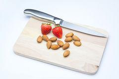 Strawberries and almonds on chopping block. Isolated on whitebackground Royalty Free Stock Image