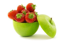 Strawberries  and the apple. Green apple filled with ripe strawberries Stock Image