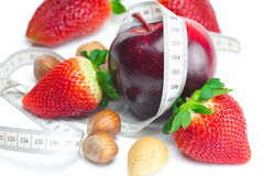 Strawberries,apple,nuts and measure tape Stock Photography