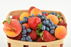 Strawberries, apricots, blueberries, peach in basket isolated on Stock Photography