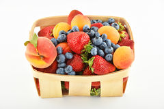 Strawberries, apricots, blueberries, peach in basket isolated on Royalty Free Stock Images