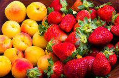Strawberries and apricots. Delicious pile of strawberries and apricots over wood Stock Image