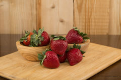 Strawberries arranged on a cutting board and an antique table Royalty Free Stock Photo
