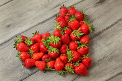 Strawberries arranged in shape of heart, placed on grey wood des stock photo