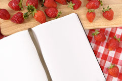 Strawberries background, recipe book, cookbook, copy space. Strawberries with blank recipe book on a chopping board and red check tablecloth Royalty Free Stock Photo