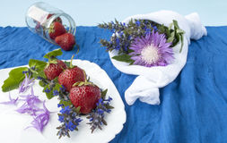 Strawberries on a background of spring flowers,. Red berries with flower petals,blue background with beautiful flowers Stock Images