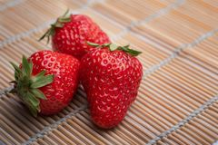 Strawberries on bamboo mats. Three red strawberries photographed indoors stock photography