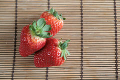 Strawberries on a bamboo table mat Stock Images