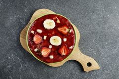 Strawberries with banana in a platter on a granite table royalty free stock image