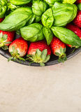 Strawberries with basil leaves in gray bowl on beige wooden background,  top view, close up, place for text, vertical Stock Photo