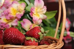 Strawberries in a basket. On a background of flowers Stock Photos