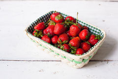 Strawberries in the basket. Beautiful wicker basket with fresh ripe strawberries on the white wooden table Royalty Free Stock Photos