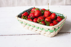 Strawberries in the basket. Beautiful wicker basket with fresh ripe strawberries on the white wooden table Stock Photos