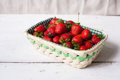 Strawberries in the basket. Beautiful wicker basket with fresh ripe strawberries on the white wooden table Stock Photography
