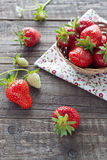 Strawberries in basket. Freshly picked strawberries in a small basket on wooden background Royalty Free Stock Photo