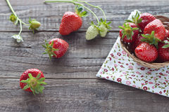 Strawberries in basket. Freshly picked strawberries in a small basket on wooden background Royalty Free Stock Image