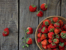 Strawberries in a basket. Wooden background royalty free stock images