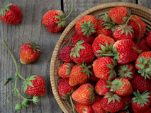 Strawberries in a basket. Wooden background royalty free stock photography