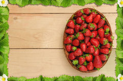 Strawberries in basket on wooden table with a frame of strawberry leaves Royalty Free Stock Photos