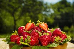 Strawberries in basket on wooden table in natural background, de Stock Image